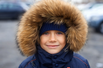 Portrait of a boy in  winter jacket with  hood on his head