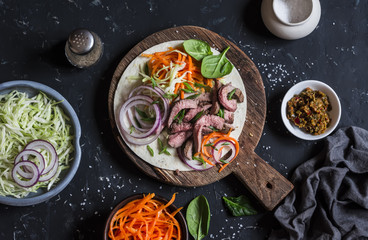 Steak tortilla with pickled carrots and cabbage on a wooden cutting board on dark background, top view