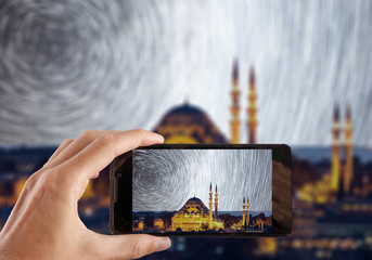 Travel concept. Hand making photo of night city with smartphone camera. Istanbul. Turkey.