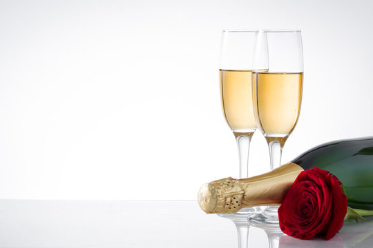 Champagne bottle, cup and red rose