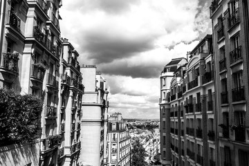 Black-white photo of view from Montmartre to summer Paris and beautiful cloudy sky. Paris, France.