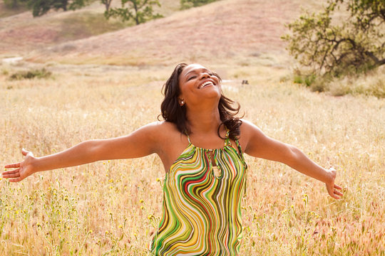 Happy African American woman with open arms.