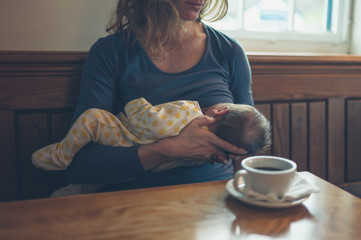 Woman breastfeeding baby in cafe