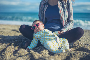 Baby wearing sunglasses on the beach with his mother