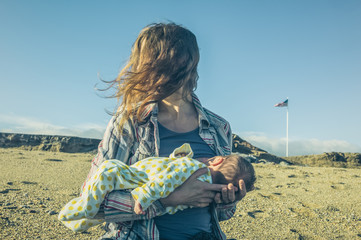 Woman breastfeeding in barren landscape with american flag