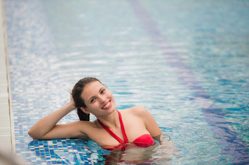 Pretty girl in fancy bikni around pool side