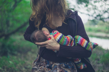 Woman breastfeeding baby in the forest