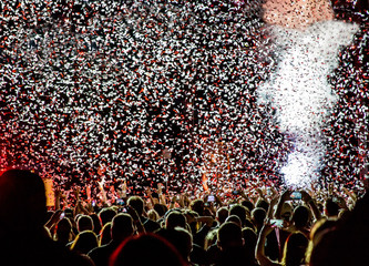 Red and white confetti falling onto a festival concert crowd silhouetted with bright lights and dry ice fog.
