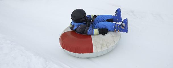 A child boy (wearing ski helmet) having fun sledding on a tube in the snow.