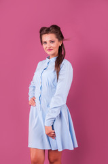 beautiful woman in a blue dress on pink background in studio