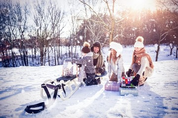 Composite image of family playing with sled on snowy field