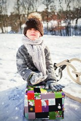 Composite image of portrait of cute boy holding present