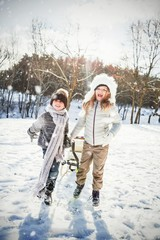 Composite image of brother and sister playing with sled on snow
