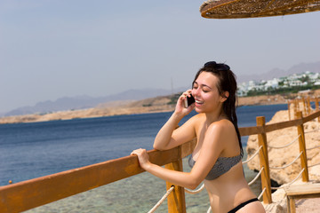 Female is talking on the phone while standing in front of wooden