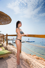 Female standing in front of wooden fence on the beach looking at