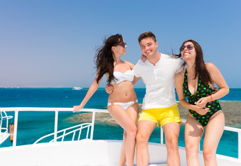 Young people laughing and standing on the yacht at a sunny summe