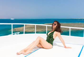 Beautiful female in black-green swimsuit lying on the deck of th