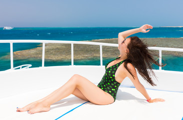 Beautiful woman in black-green swimsuit lying on the deck of the