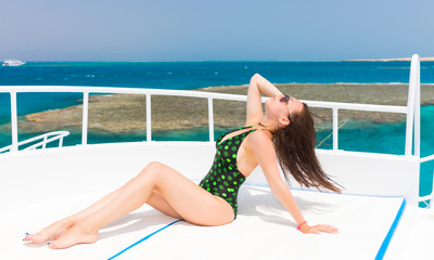 Beautiful young woman in black-green swimsuit lying on the deck