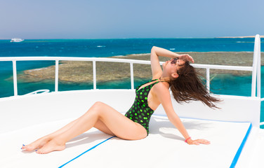 Young woman in black-green swimsuit lying on the deck of the yac