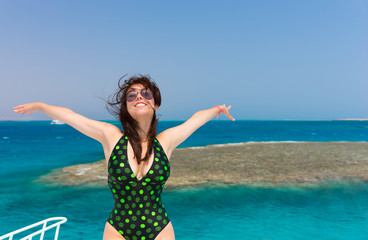 Smiling brunette in black-green swimsuit standing on the yacht a