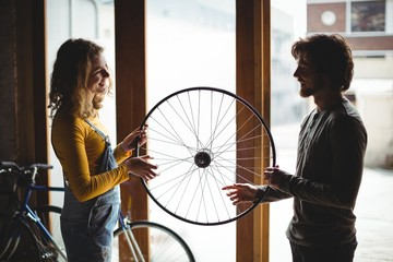 Mechanics interacting while examining a bicycle wheel