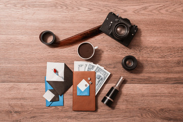 Cup of black coffee, old black vintage camera, film, lens, American dollars, dice, notebook, open envelope with a flower roses, telescope lie on the wooden background. Going on a trip. Flat lay