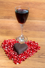 Glass of red wine and heart from pomegranate seeds and chocolate. Declaration of love on Valentine's Day.