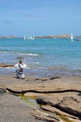 Un randonneur s'arrête sur un rocher pour prendre une photo du paysage de mer à Trégastel en Bretagne