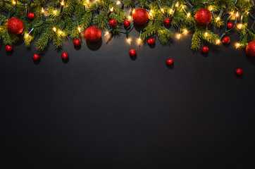 Christmas decoration background over black chalkboard, top view. Horizontal photo of decorations taken from above with copy space for text and other web or print design elements.