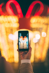 Close view of woman hand holding mobile phone and taking picture of Christmas decoration