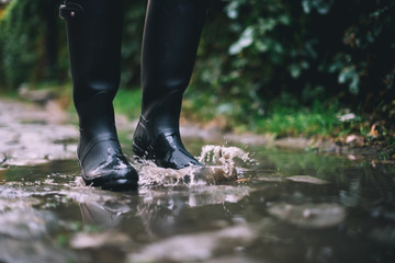 Woman in black rubber boots standing in a puddle with autumn leaves while it's raining.