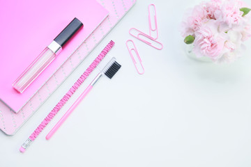 A feminine pink desktop mock up with pink lipstick, notebooks, paper clips, a pencil and miniature pink carnations on a white isolated background for a business concept.