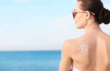 Woman with sun protective lotion in sun shape on shoulder