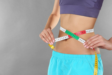 Woman measuring her waist on color background