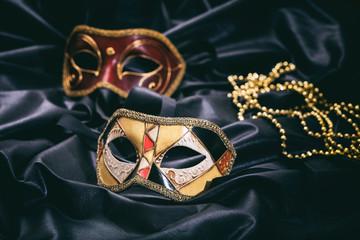 Carnival masks on black satin background