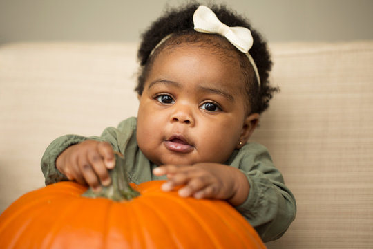 Cute baby girl with a  pumpkin.