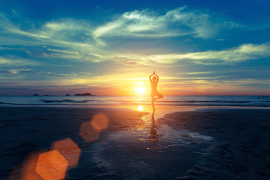 Yoga silhouette at sunset on the sea shore. Calm and self-control.