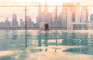 Kuala Lumpur, Malaysia city skyline at sunrise. Swimming pool on roof top with beautiful city view kuala lumpur malaysia.