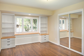 Emty room with wooden floor and built in shelves.