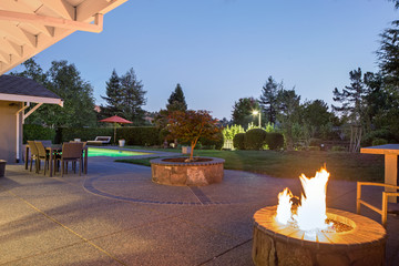Fire pit with amazing back yard and pool at night.