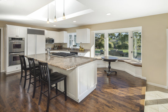White Kitchen interior with kitchen island, granite counter tops