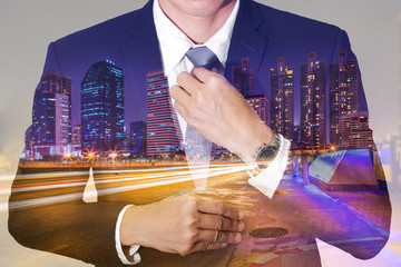 Double exposure of businessman held necktie dress to look good, urban, city and street at night as preparation and leadership concept.