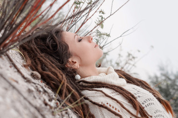 attractive young woman in sweater lying on ground