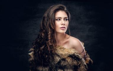 Sensual brunette female dressed in a fur coat.
