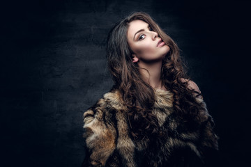 Brunette woman with long curly hair dressed in a fur coat.