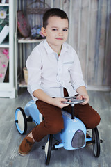 The boy in the white shirt riding a baby blue car, Provence style, full length.