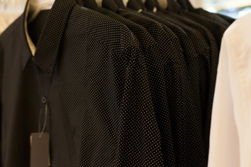 Black polka dot and white shirt hanging on a rack in a row of shops. Fashion garment business