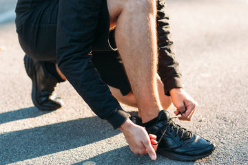 Shoelaces tying close-up. Man correct footwear before walk. Sportsman preparing for race