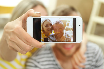 Happy couple taking selfie with phone in room